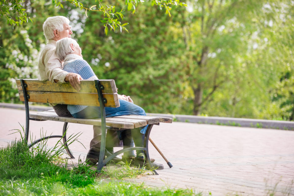 elderly couple resting on a bench in park