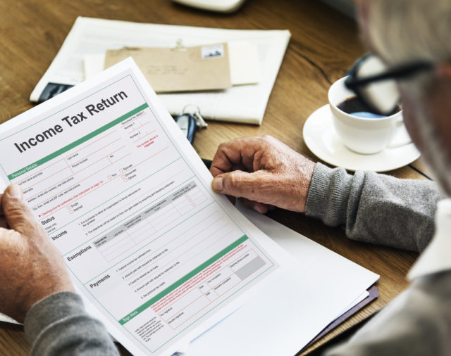 man holding income tax return document