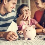 Kid putting money in piggybank with parents