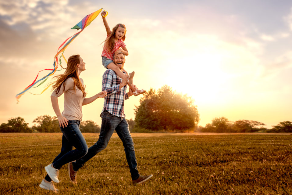 family running across field with kite
