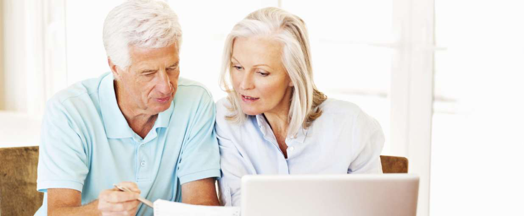 elderly couple going over paperwork in front of computer