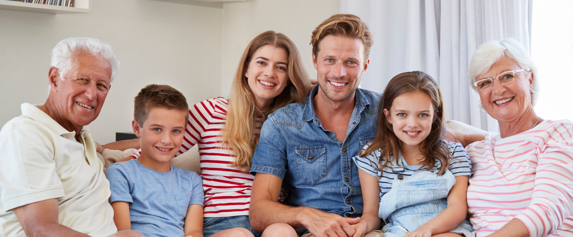 multi-generation family sitting on sofa at home
