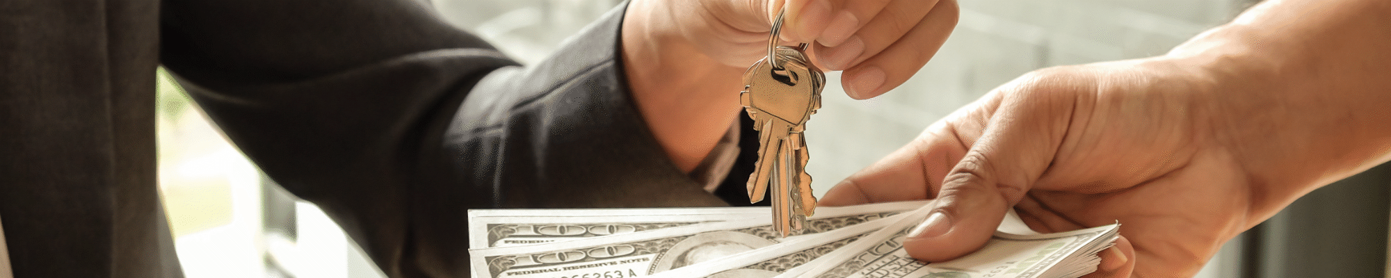 hands exchanging money for keys to new home