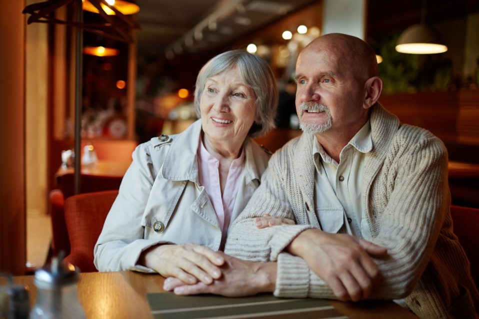 elderly couple sitting at restaurant looking out the window