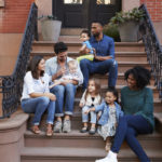 two families with kids sitting on front stoop
