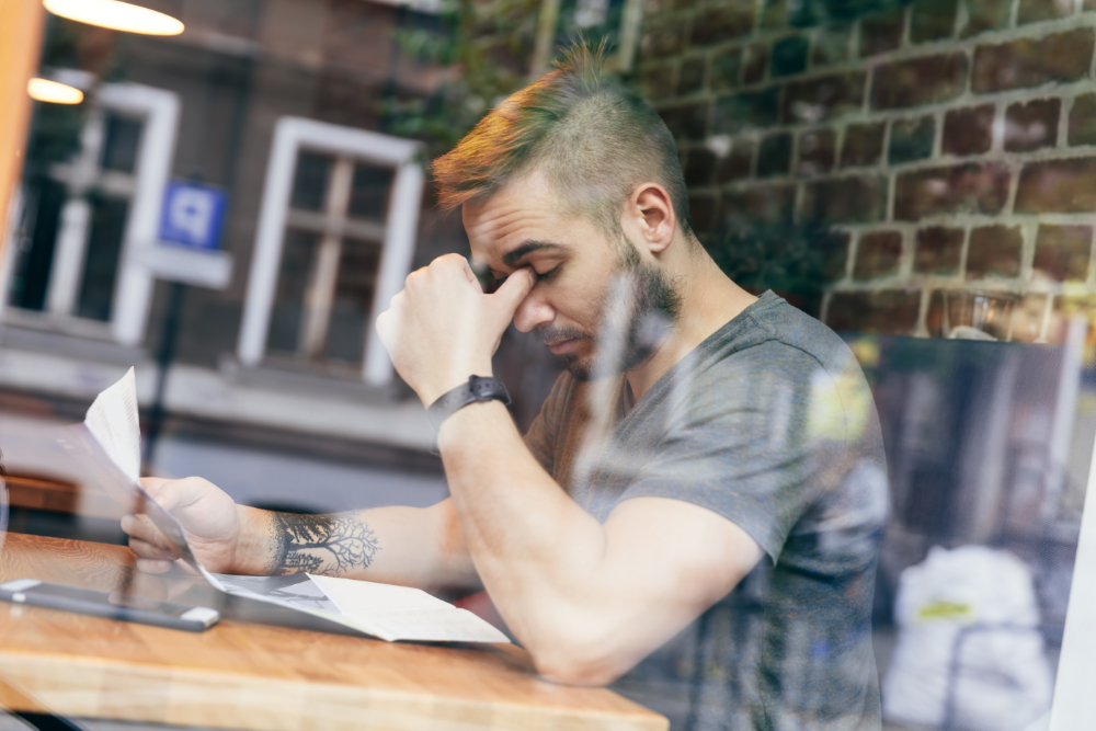 tired and stressed man sitting at table by window