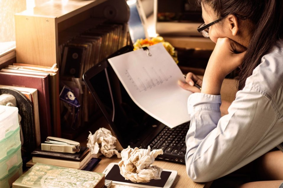 woman overlooking charts at messy desk